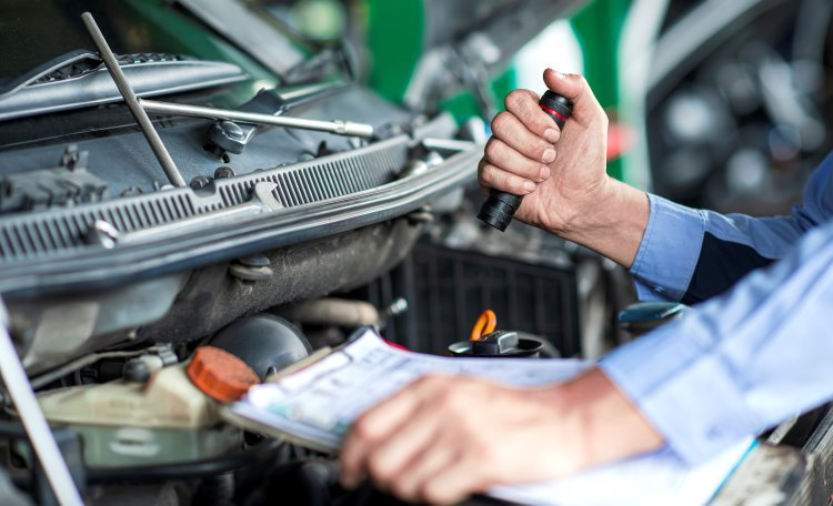 Bilmekaniker håller i ficklampa och ett protokoll, tittar ner i bilmotor
