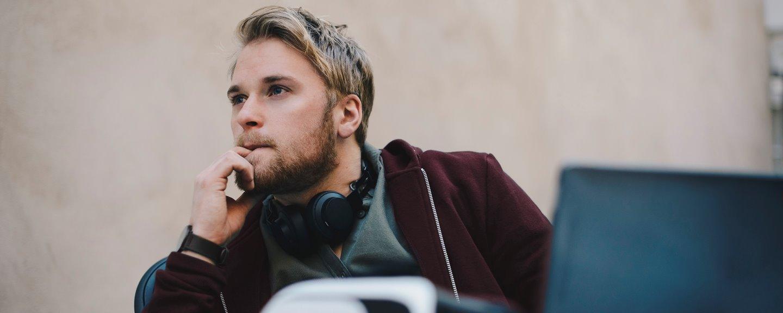 Fundersam ung man sittandes vid laptop