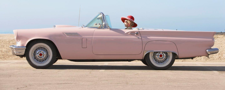 Äldre kvinna som kör rosa cabriolet