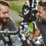 Två glada män vid motorcykel i trädgård