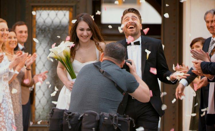 Fotograf fotograferar nygift par utanför kyrka