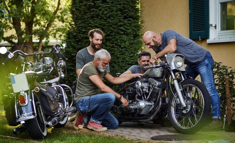 Fyra vänner vid en motorcykel i trädgård