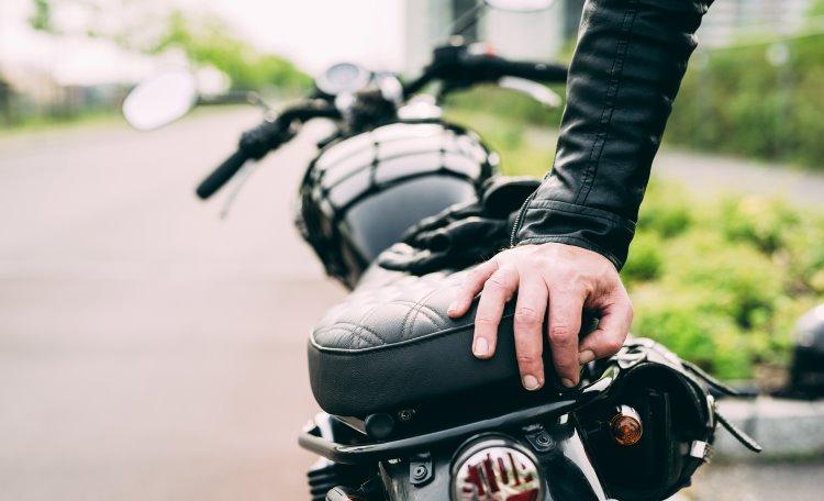 Hand av manlig motorcyklist som lutar sig på motorcykeln