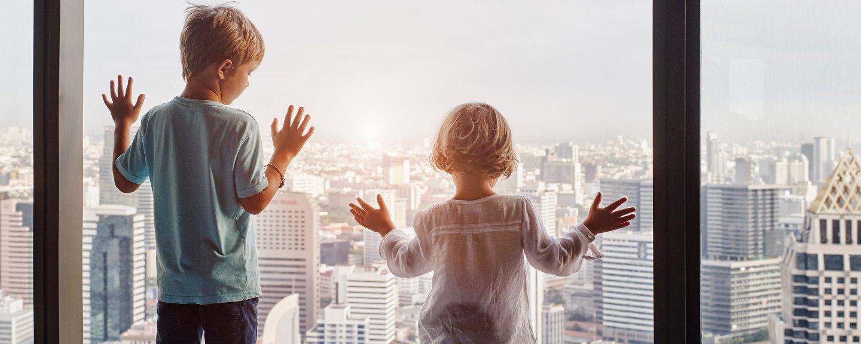 Pojke och flicka tittar ut över storstad vid panoramafönster på hotellrum