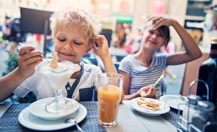 Pojke och flicka äter glass på café