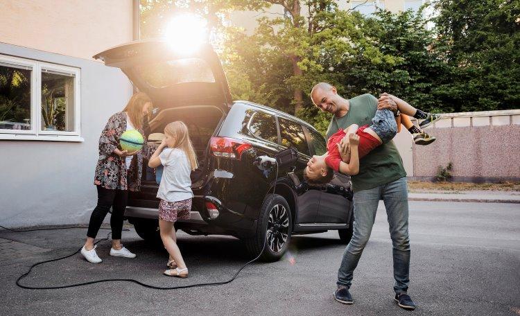 Pappa skojar med son med mamma och dotter som packar bil på uppfart