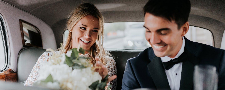 Nygift par i bröllopskläder sitter i bil