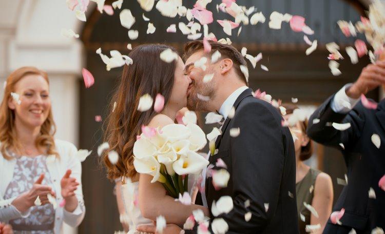 Bröllopspar som kysser varandra på kyrkotrappa