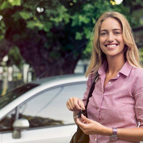 Kvinna står utanför sin bil med en mobil i handen