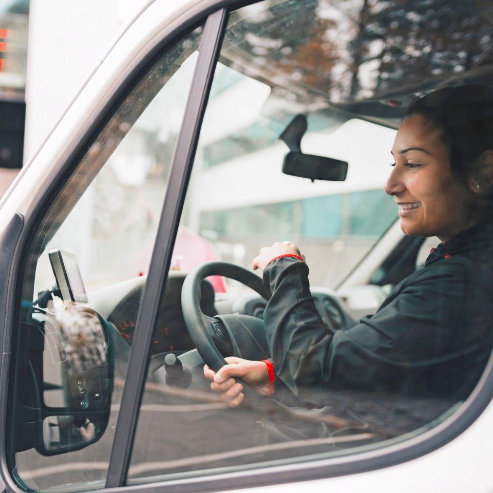 Kvinna i yrkeskläder kör minilastbil i stan