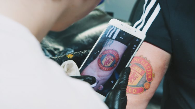 Tatuerare fotar av Nisses tatuering av Manchester United-logotypen med sin mobil.