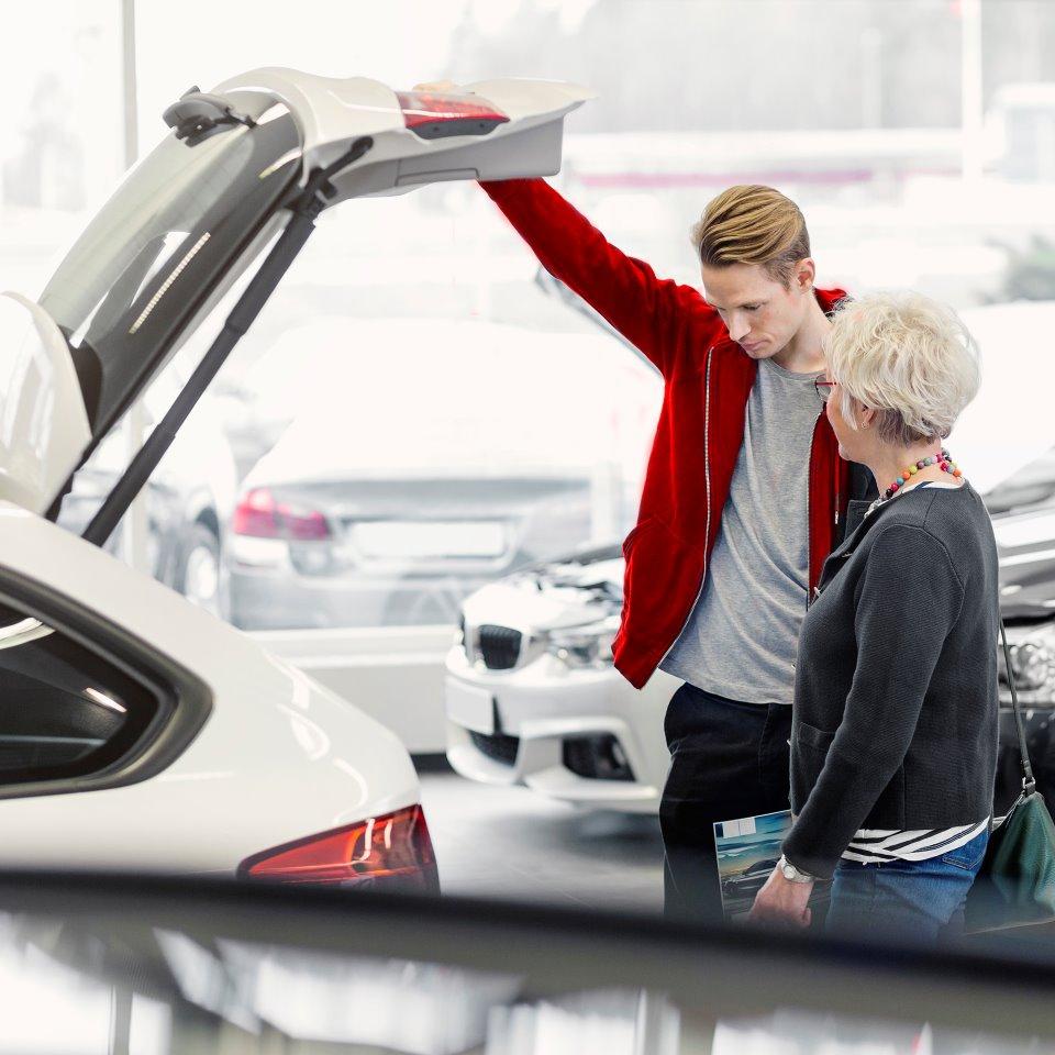 Ung man och äldre kvinna i bilhall som tittar ner i motorn på en silvrig bil