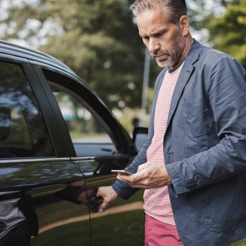 Man använder mobiltelefon medan han öppnar bildörr
