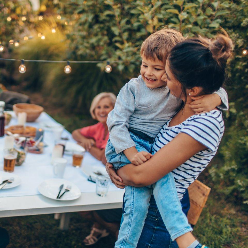 En kvinna håller en pojke i famnen i en somrig trädgård.