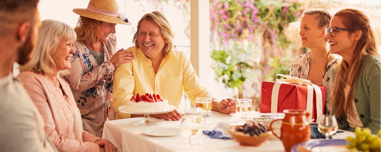 Medelålders man i gul tröja, omgiven av släkt och vänner, sitter vid födelsedagsdukat bord
