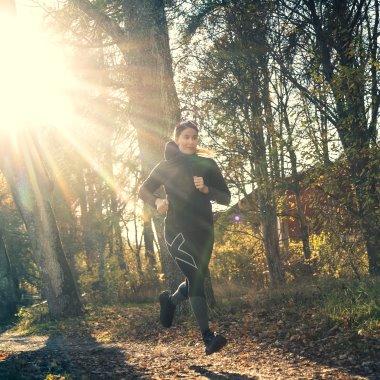 Annie Thorén springer en höstdag med solen i ryggen.