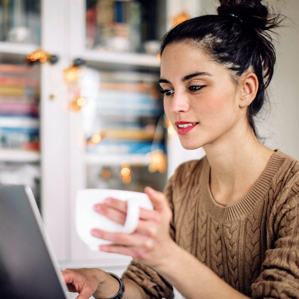 Ung kvinna med kaffekopp i handen framför laptop