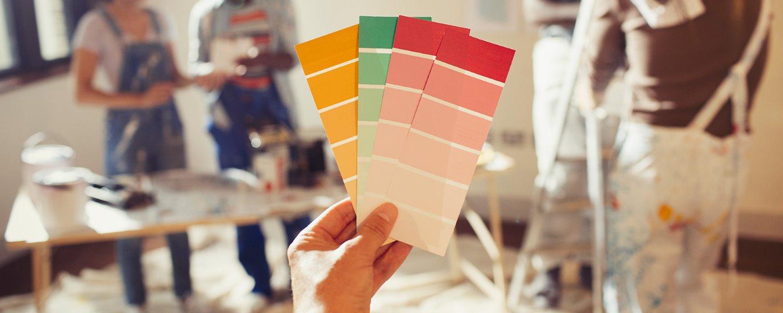 Närbild på hand som håller i olika färgprover med vänner som målar om vardagsrum i bakgrunden