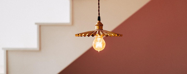 Låg vinkel av upplyst glödlampa som hänger mot trappa
