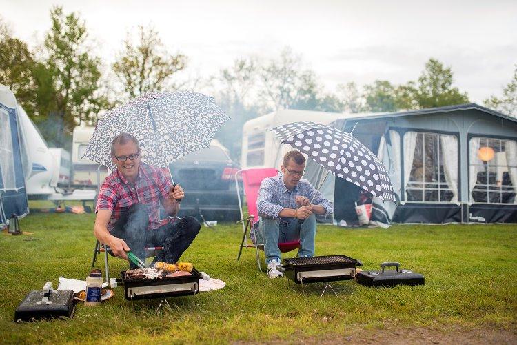 Män som grillar i regn utanför husvagn