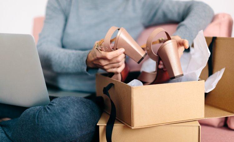 Beskuren bild av en kvinna med en bärbar dator i knät som packar upp skor från ett paket