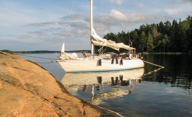 Segelbåt ligger förtöjd vid klippa