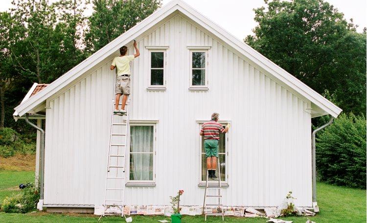 Två män står på stegar och målar vit trävilla