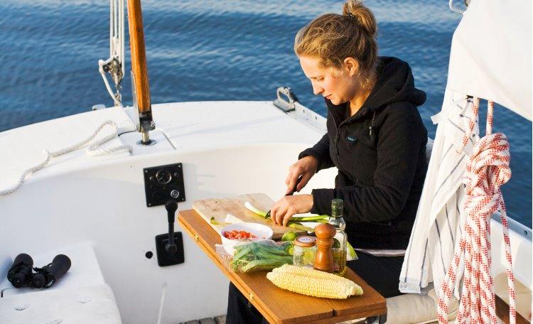 Kvinna som förbereder måltid på segelbåt
