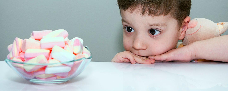 Pojke som kramar gosedjur och tittar intresserat på en skål med marshmallows
