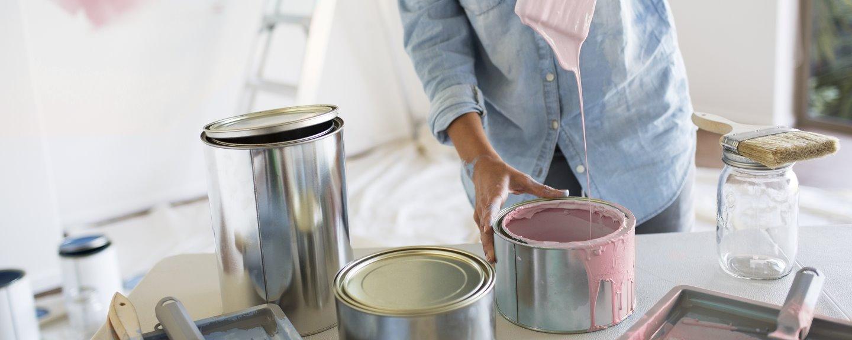 Kvinna som håller i målarpensel med rosa färg